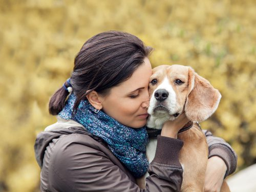 A lady with her pet dog contemplating at-home pet euthanasia with Time2SayGoodbye.